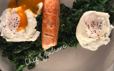 Poached eggs and salmon served on a bed of spinach and Kale